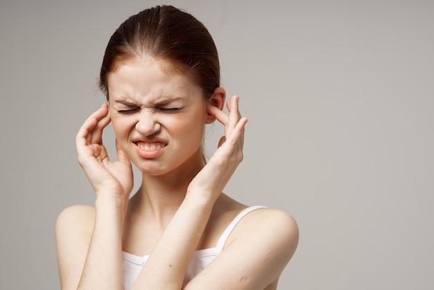 病気の女性の耳の痛みの健康問題の不満明るい背景。高品質の写真