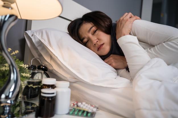 病気の女性がベッドで冷たく感じて