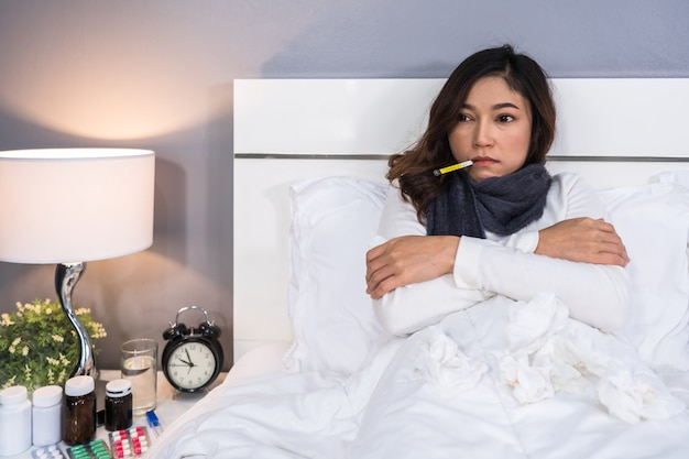 Sick woman feeling cold and using thermometer to checking her temperature in bed
