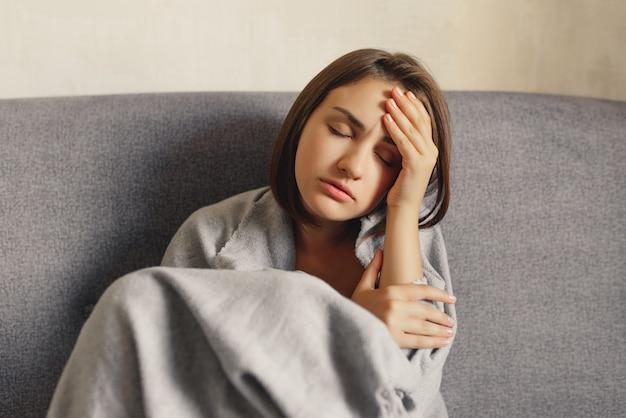 ウールの格子縞に包まれた頭痛、凍えを感じている病気の女性。
