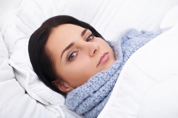 Sick woman. flu. girl with cold lying under a blanket holding a tissue