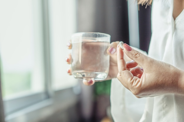 Sick woman hand taking medicine with glass of water