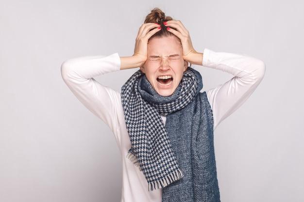Больная женщина имеет температуру, держится за голову и плачет. студия выстрел, изолированные на сером фоне