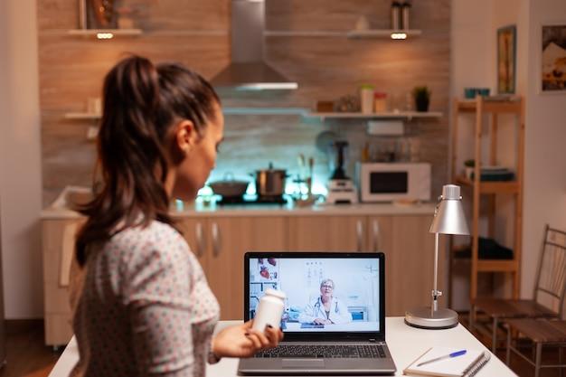 Больная женщина, держащая бутылку таблеток во время видеоконференции, прося совета. врач, консультирующий больного пациента из офиса больницы во время виртуальной конференции, устройство, лекарство, прием