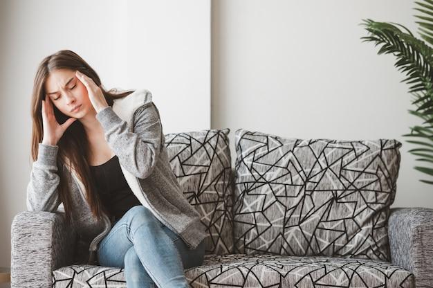 Больная женщина, держащая ее голову, чувствует боль и страдает от головной боли