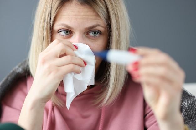 Больная женщина, держащая инфракрасный термометр и бумажную салфетку. концепция амбулаторного лечения