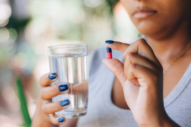 Sick woman holding pill of medicine and a glass of water. taking medicine. concept of person and self-medication. health treatment. depression, insomnia, pain