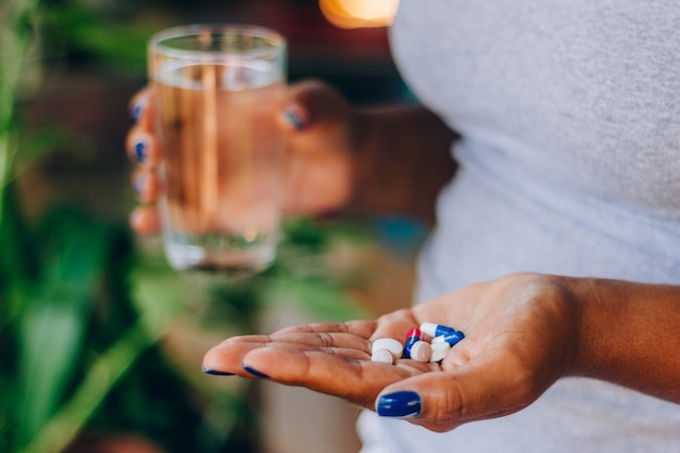 Sick woman holding several medicines in her palm and a glass of water. taking medicine. concept of person and self-medication. health treatment