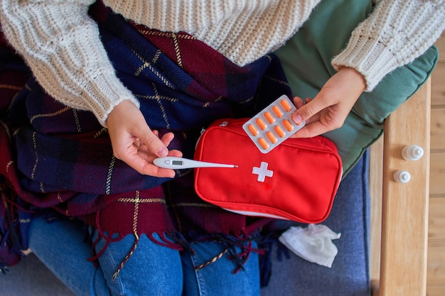 Sick woman holds thermometer and suffering from high fever. first aid kit with medicines for the treatment of flu and colds. top view