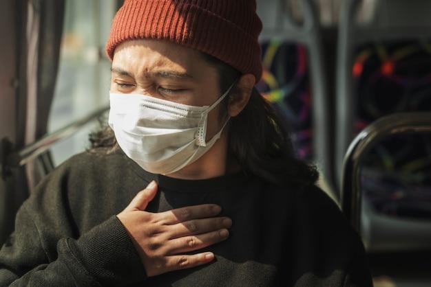 Больная женщина в маске испытывает затрудненное дыхание во время пандемии коронавируса