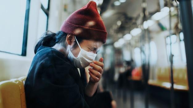 코로나바이러스 전염병 동안 기차에서 재채기하는 마스크를 쓴 아픈 여성