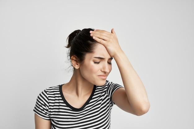 首の孤立した背景の縞模様のtシャツの痛みの病気の女性
