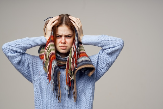暖かいセーターとスカーフの健康上の問題の鼻水で病気の女性