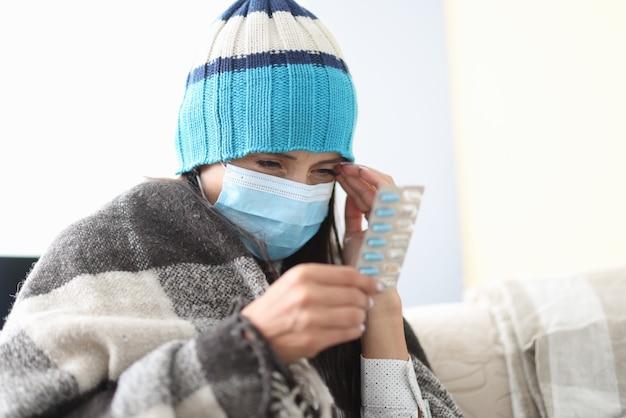 自己隔離の毛布の下で帽子をかぶった病気の女性は彼女の手で丸薬を保持します