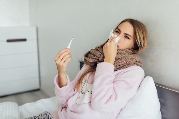 高熱とインフルエンザでベッドに横たわって、彼女の鼻を吹く家庭服の病気の女性