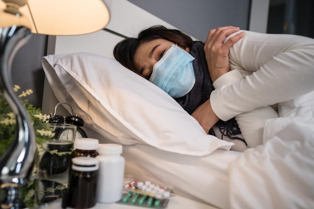 Больная женщина в медицинской маске чувствуя холод и страдая от вирусной болезни и лихорадки в кровати, концепции пандемии коронавируса.