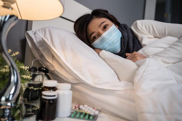 Больная женщина в медицинской маске страдая от вирусной болезни и лихорадки в кровати, концепции пандемии коронавируса.