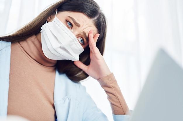 Больную женщину в защитной медицинской маске, используя ноутбук, сидя на полу у себя дома.