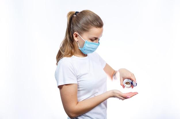 온도계와 약을 손에 들고 보호용 의료 외과용 마스크를 쓴 아픈 여성은 바이러스 치료를 받습니다. 자가 격리 및 약물 치료