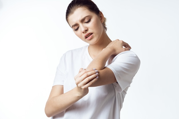 白いtシャツの痛みの健康問題の不満の病気の女性