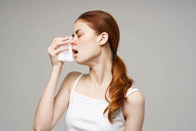Больная женщина в белой футболке с шарфом на изолированном фоне