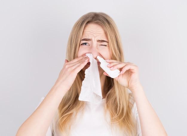 Больная женщина закапывает капли в нос