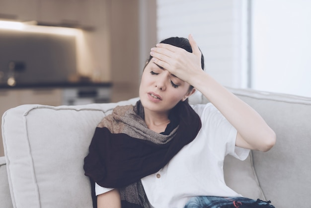Sick woman is sitting on a couch with a headache.