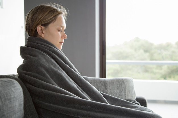 Sick woman keeping her eyes closed, meditating at home
