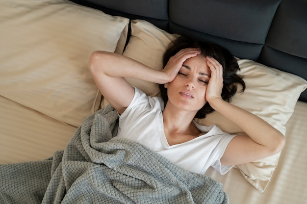 Donna malata sdraiata a letto colpo medio