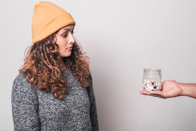 白い背景の人の手に丸薬のボトルを見て病気の女性