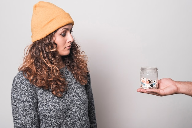 Sick woman looking at pills bottle on man's hand against white background
