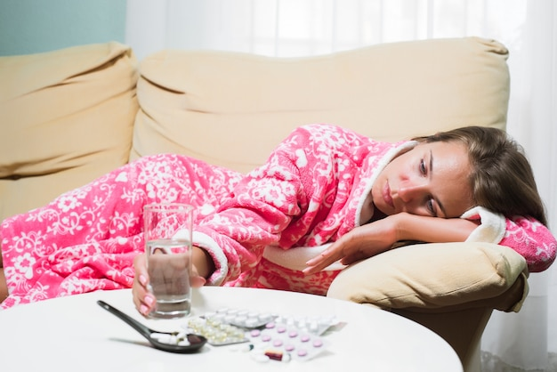 Sick woman lying in bed in dressing gown looking at thermometer and pills