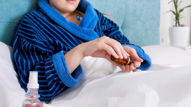 Sick woman lying in bed and pouring pills from glass container on hand.