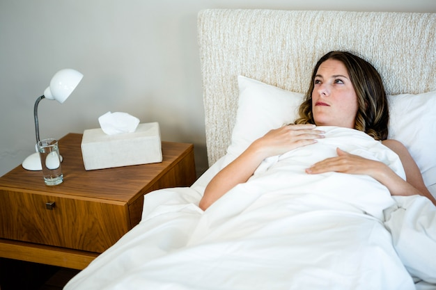 Sick woman lying in bed surrounded by tissues and water