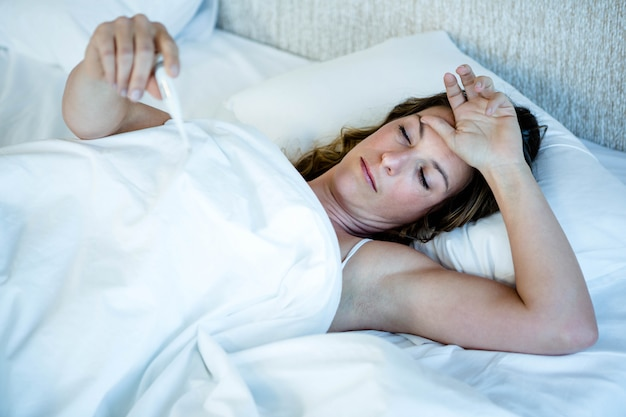 Sick woman lying in her bed, reading a thermometer