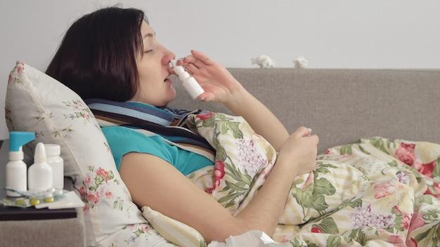 病気の女性が自宅のベッドに横たわって、鼻にスプレーします。