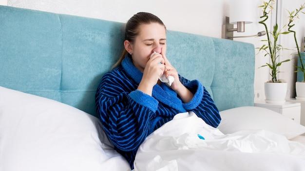 鼻をかむと鼻スプレーを使用してベッドに横たわっている病気の女性