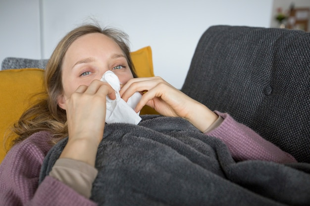 Sick woman lying on sofa at home, blowing her nose with napkin
