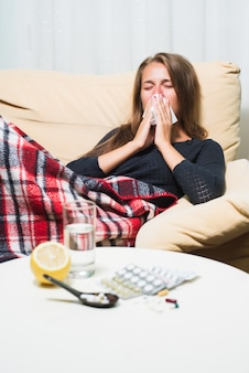 Sick woman lying on sofa under wool blanket sneezing and wiping nose
