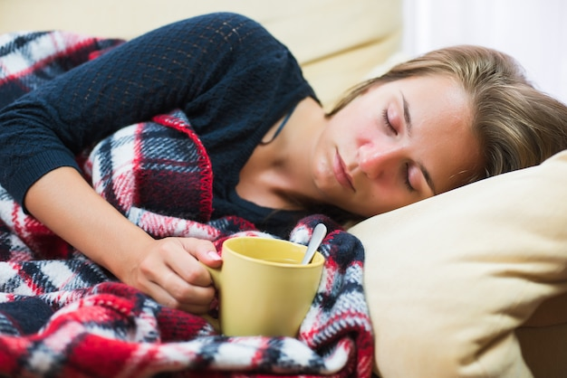 Sick woman lying on sofa under wool blanket with cup of tea