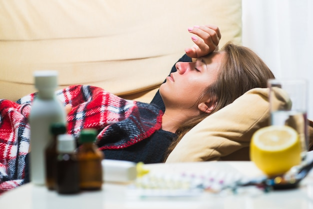 Sick woman lying on sofa under wool blanket