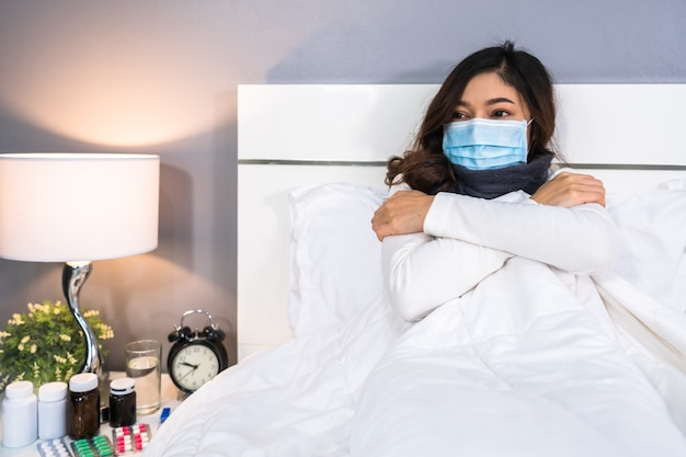 Sick woman in medical mask feeling cold and suffering from virus disease and fever in bed, coronavirus pandemic concept.