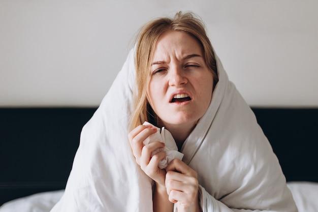 Больная коронавирусом, лежа в постели, выздоравливает от болезни дома сморкается и кашляет оставайтесь дома