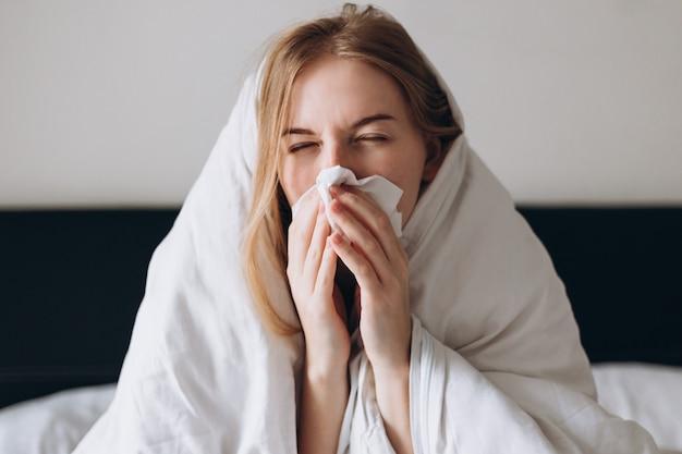 Больная женщина вирусом короны, лежа в постели, выздоравливает от болезни дома
