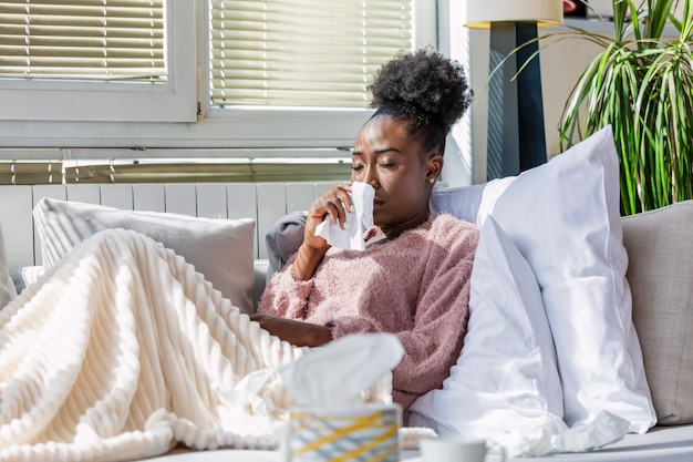 彼女の鼻を吹いているソファの上の病気の女性