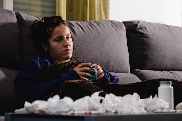 自宅のソファで温かい飲み物を飲んでいる病気の女性