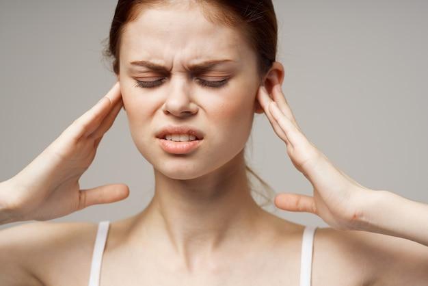 Больная женщина с плохими нарушениями слуха в белых футболках.
