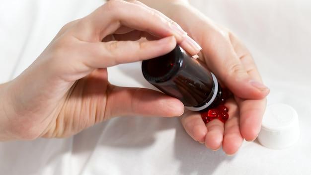 Больная женщина лить таблетки и таблетки под рукой из стеклянной бутылки.
