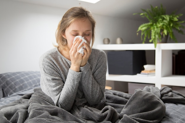 Sick woman sitting in bed, blowing nose with napkin