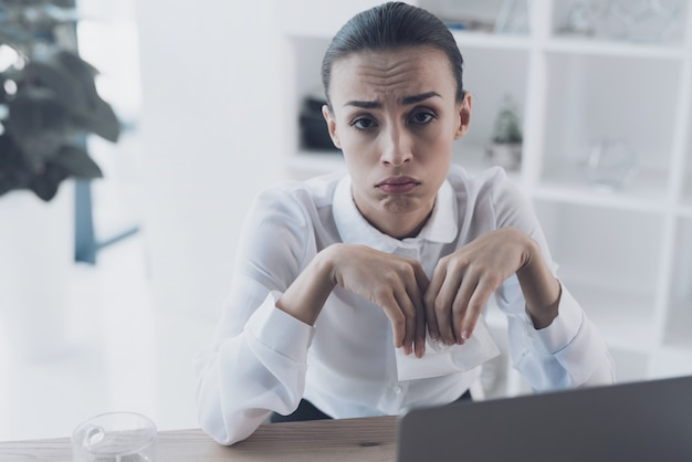 Sick woman sitting at her workplace in the office